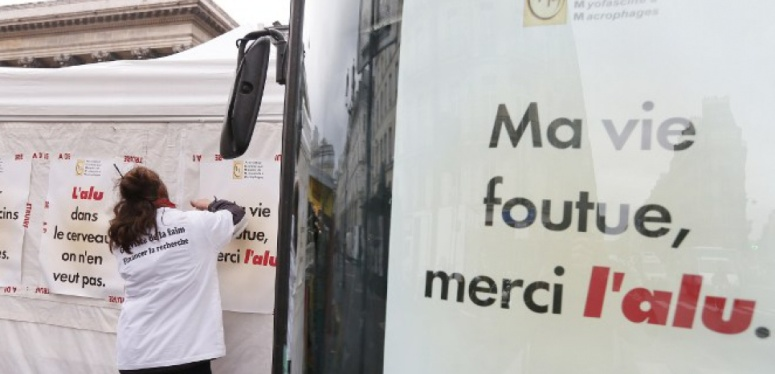 """A woman of French Macrophagic Myofasciitis patient support association E3M, hangs placards on a tent at the start of a 'symbolic indefinite hunger strike', on November 27, 2012  in front of the former Stock Exchange quarters in Paris, to ask for reinforced research efforts on vaccine-derived aluminium. Placard in the foreground reads: """"My life is over, thanks aluminium."""" AFP PHOTO KENZO TRIBOUILLARD"""